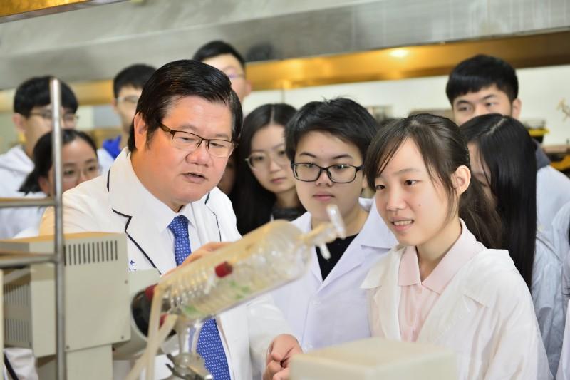 洪明奇校長親自指導研究生科學研究要領。(記者高秋敏翻攝)