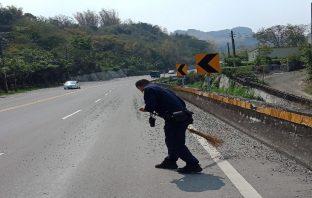 碎石散落路面 日正當中警揮汗清除維護用路人安全。(記者張文晃翻攝)