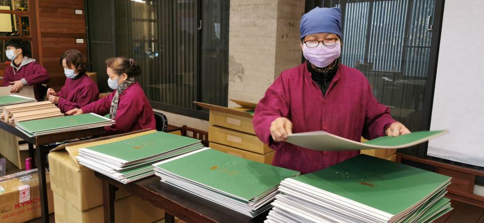 菩薩寺志工趕工製作月曆,今年已經發行到第三版。(葉志雲攝)